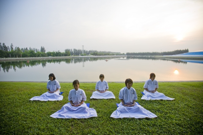 buddhist girls meditating at sunrise by pool