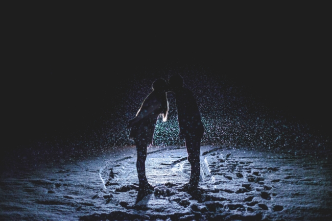couple romantic kissing at night in the snow love