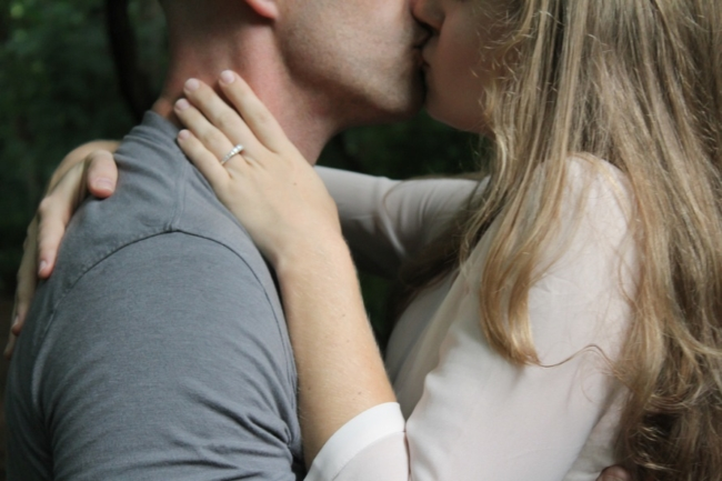 couple kissing with engagement ring