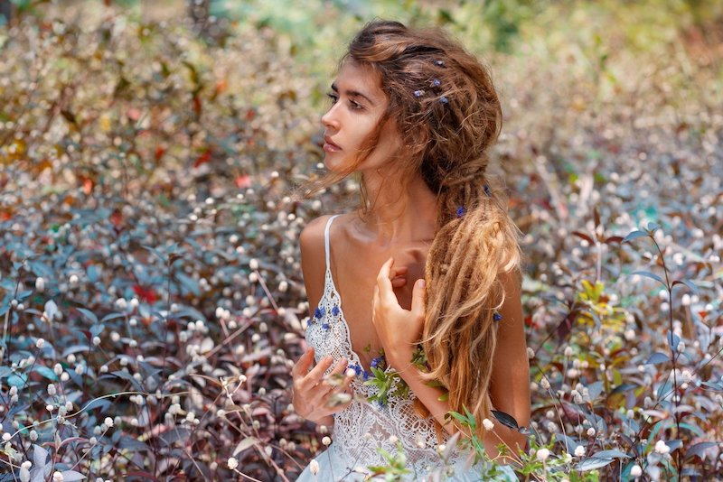 boho girl with dreadlocks in a white dress, sitting in a field