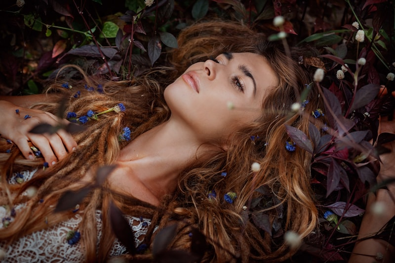 hippy woman lying on the ground covered with flowers and leaves in her hair