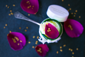 Natural organic face cream in a green bottle with rose petals. Beauty. Slate