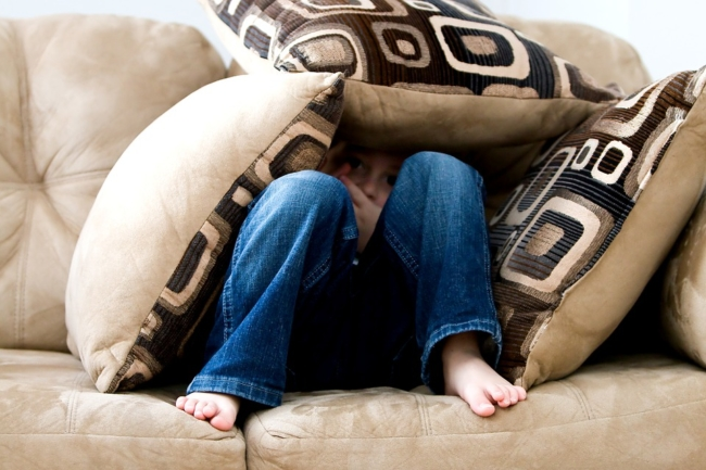 child-boy-hiding-under-cushions