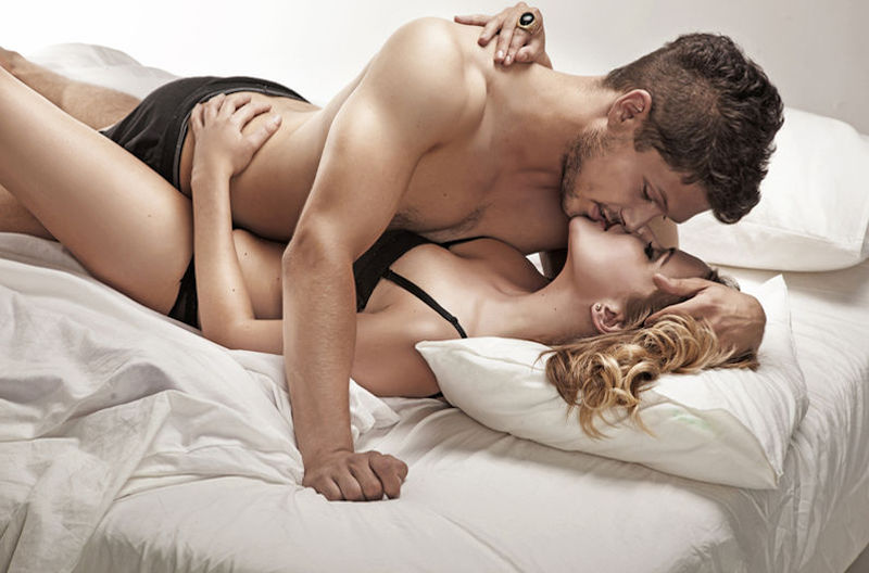 couple passionately kissing in bed