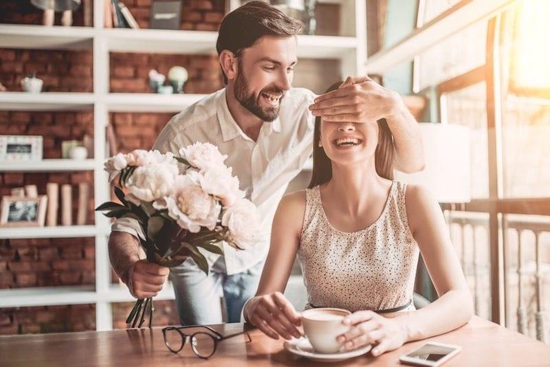 man surprising girlfriend with flowers