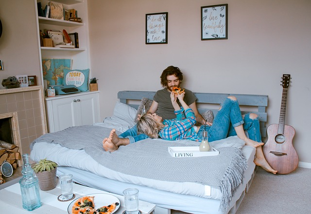 room couple in bed together eating pizza, girl is feeding guy pizza, lying on his lap