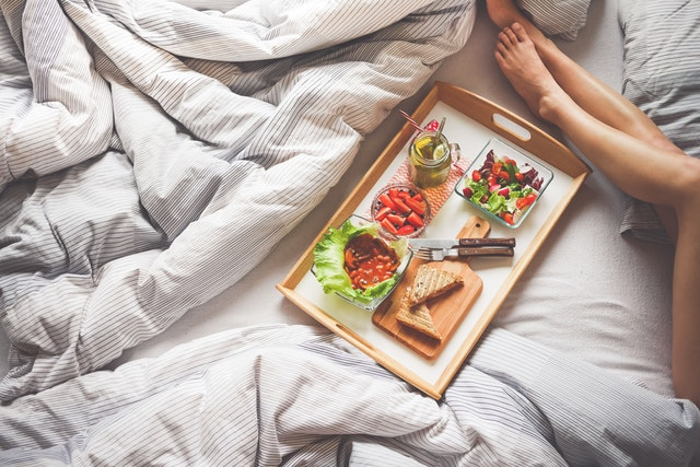 woman eating lunch on her bed, legs, vegetarian meal