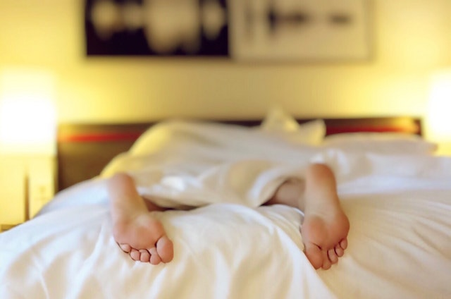 woman lying in bed alone just her feet showing under the duvet covers