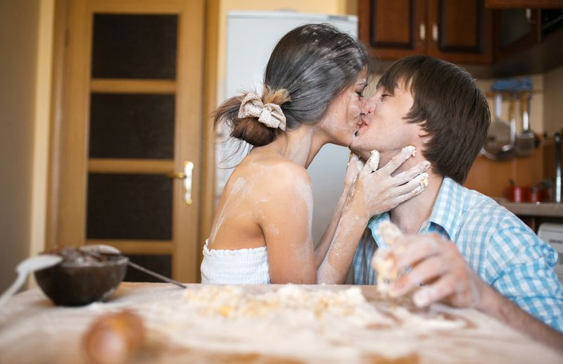 messy couple kissing in the kitchen having fun
