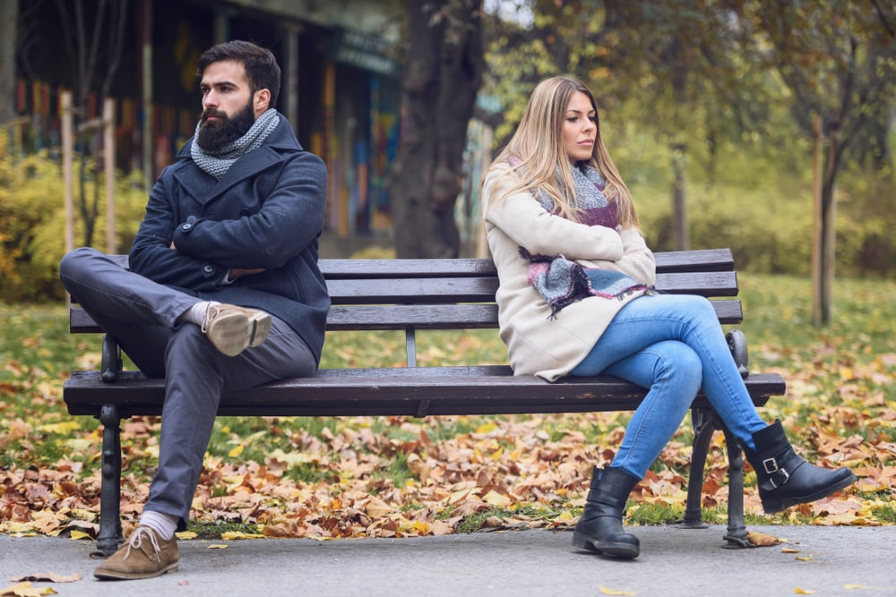 couple looking away from each other on a bench, upset, relationship problems