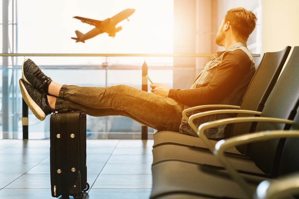 man waiting at airport with feet on suitcase looking at plane