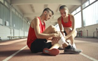 woman helping sportsman with leg injury during cardio exercise