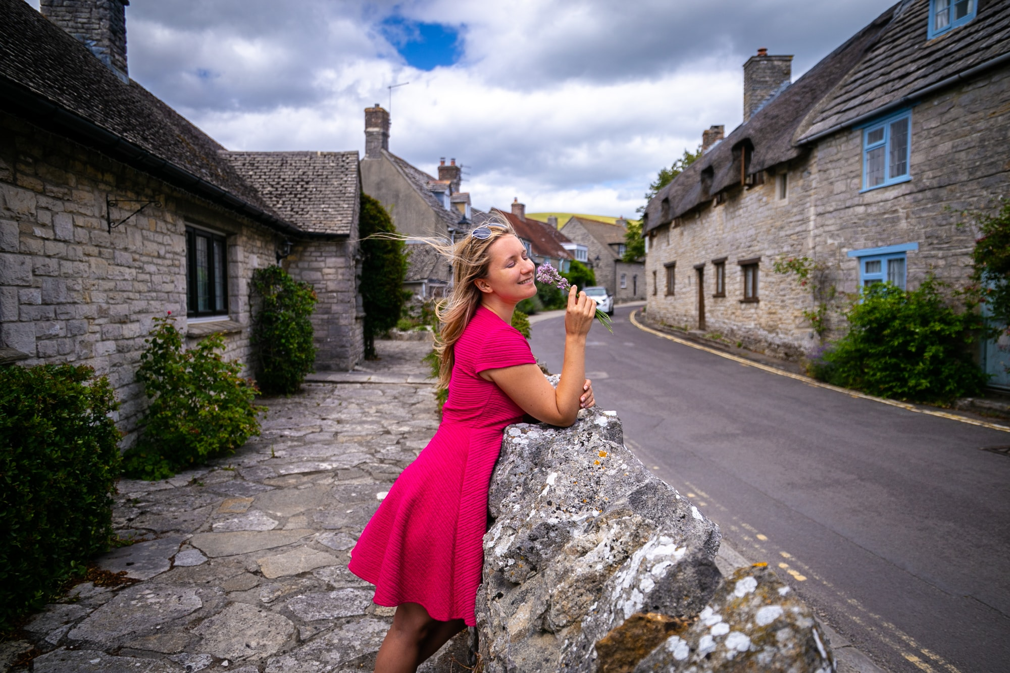 Anya Andreeva smelling lavender in British village in pink dress