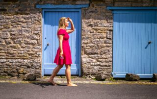 Anya Andreeva walking in pink dress by blue door