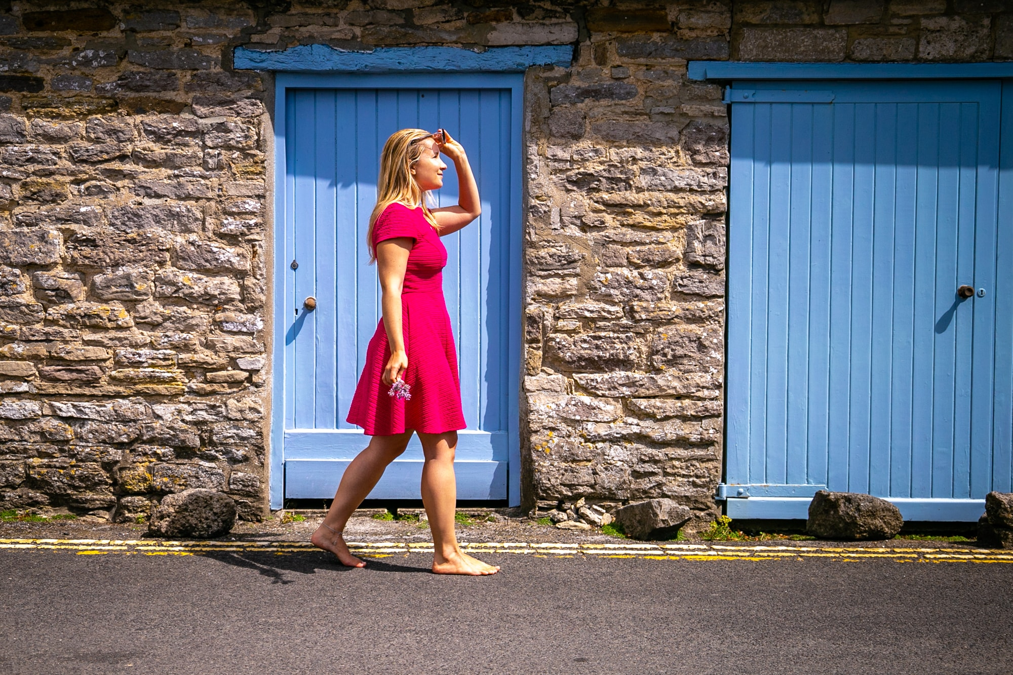 Anya Andreeva walking in pink dress by blue door